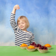 Stock Photo: Little girl dancing behind cherry and peach jelly tarts
