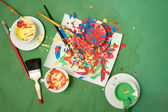 Cups with saucers full of bright paints and some painting instruments — Stock Photo