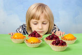 Little pretty girl looking sadly at cherry and peach jelly tarts — Stock Photo