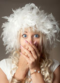Surprised woman with big blue eyes and a plume hat — Stok fotoğraf
