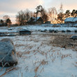 Stock Photo: Houses next to icy meadow