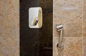 Verchroomd strooi douche en kraan bij marmeren muur — Stockfoto