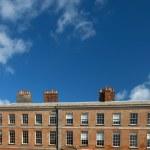 Red brick Irish building with row of chimney — Stock Photo