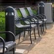Stock Photo: Row of metal armchairs on sand ground