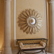 Stock Photo: Antique settee and starburst convex mirror