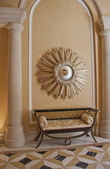 Antique settee and starburst convex mirror — Стоковое фото