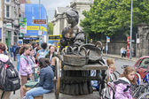 The statue of Molly Malone along Grafton Street in front of Trinity College Dublin surrounded by students — Stock Photo