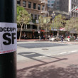 Stock Photo: Occupy SFrancisco sticker placed on pole announces start actions of new public movement