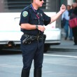 Muscular US policemen beconing somebody at the street - Stock Photo