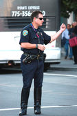 Muscular US policemen beconing somebody at the street — Stock Photo
