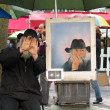 Public painter on Montmartre screening his face and instead showing self-portrait — Stock Photo #39768429