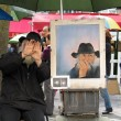 Public painter on Montmartre screening his face and instead showing self-portrait — Stock Photo