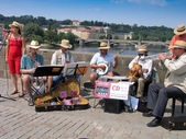 PRAGUE, CZECH REPUBLIC - JUNE 15, 2006: Orchestra of street musicians play at Charles Bridge on June 15, 2006, Prague, Czech Republic. Annually Prague is visited by more than 3,5 million tourists — Stock Photo