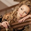 Alluring blonde woman in black dress and jewelry with hairstyle and makeup. Beautiful girl in luxury interior. Rich lady. Sexy Blonde Woman In Black - Stock Photo