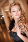 Alluring blonde woman in black dress and jewelry with hairstyle and makeup. Beautiful girl in luxury interior. Rich lady. Sexy Blonde Woman In Black — Stock Photo