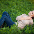Beautiful woman resting on spring nature outdoors. Happy girl relaxing in summer park — Stock Photo