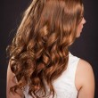 Stock Photo: Beautiful long Red hair. womwith healthy curly Hairs and stylish hairstyle. Health and beauty products. Teenager girl beauty model. fashion lady with long curly glossy hairs at studio.
