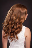 Beautiful long Red hair. woman with healthy curly Hairs and stylish hairstyle. Health and beauty products. Teenager girl beauty model. fashion lady with long curly glossy hairs at studio. — Stock Photo