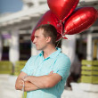 Smiling young man waiting for girlfriend with balloons.  — Stock Photo
