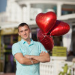 Smiling young man waiting for girlfriend with balloons. — Stock Photo #32655475