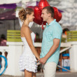 Teenage couple embracing on dating with bunch of balloons hearts — Foto de Stock