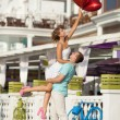 Teenage couple embracing on dating with bunch of balloons hearts — Stockfoto