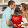 Man and woman holding balloon in shape of hearts — Stock Photo