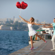 Teenage couple embracing on dating with bunch of balloons hearts. — Stock Photo #32655611