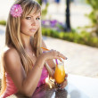 Beautiful young woman sitting in cafe with fresh orange juice. — Stock Photo