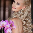 Beautiful blonde young woman with orchid flowers bouquet. — Photo