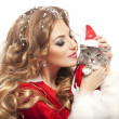 Beautiful christmas woman in Santa Clause costume holding a cat. — ストック写真