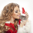 Beautiful christmas woman in Santa Clause costume holding a cat. — Stock Photo