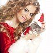 Beautiful christmas woman in Santa Clause costume holding a cat. — Stock Photo #32657115