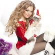 Woman in Santa Clause costume holding a cat. — Photo