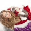 Woman in Santa Clause costume holding a cat. — Stock Photo