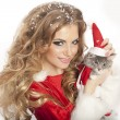 Beautiful christmas woman in Santa Clause costume holding a cat. — Stock Photo #32657193