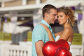 Teenage couple embracing on dating with bunch of balloons hearts. — Stock Photo