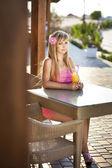 Mooie jonge vrouw in café met verse jus d'orange. — Stockfoto