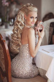 Gorgeous blonde woman with red wine glass in luxury restaurant. — Stock Photo