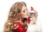 Krásná vánoční žena v kostýmu santa doložka drží kočku. — Stock fotografie