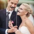 Bride and groom with funny false mustache — Stock Photo