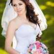 Happy bride in veil holds wedding bouquet  — Stock Photo