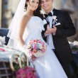 Groom and beautiful bride near car — Stockfoto