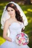 Happy bride in veil holds wedding bouquet — Stock Photo