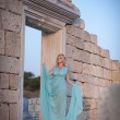 Woman in Greek style on sunset near ancient ruins. — Stock Photo