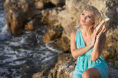 Woman with seashell in Greek style at sunset. — Stockfoto