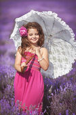 Girl with umbrella in lavender meadow — Stock Photo