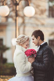 Bride and groom with roses bouquet — Stock Photo