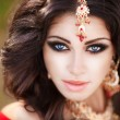Beautiful Indian Woman in Traditional red dress and golden jewelry outdoors — Stock Photo #36507961