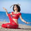 Beautiful Indian woman dancing with golden sword outdoors — Stock Photo